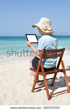 Cropped image of woman using digital tablet at beach
