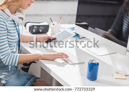 cropped image of woman using tablet and computer at modern office