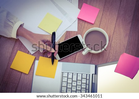 Cropped image of woman writing on sticky notes in her office - stock photo