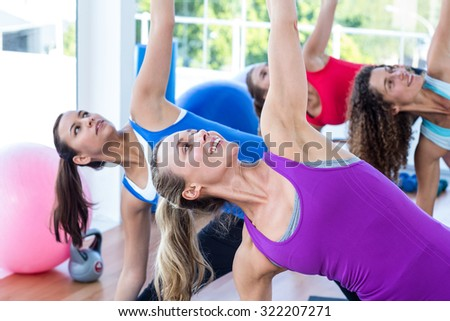 Cropped image of women doing side stretch in fitness studio - stock photo