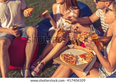 Cropped image of young beautiful people in casual clothes and sun glasses eating pizza, talking and smiling, sitting on bean bag chairs while resting outdoors - stock photo