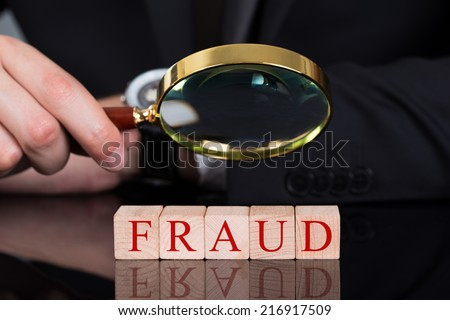 Cropped image of young businessman examining Fraud blocks through magnifying glass on desk - stock photo