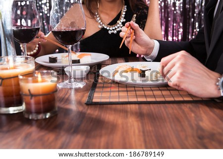 Cropped image of young couple having meal at restaurant table - stock photo