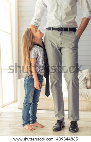 Cropped image of young father in classic wear and his cute little daughter standing in the room. Girl in father's tie is looking at her dad and smiling - stock photo