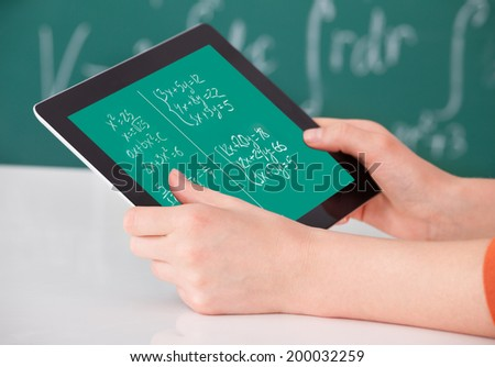 Cropped image of young female student solving math's problem on digital tablet in classroom - stock photo