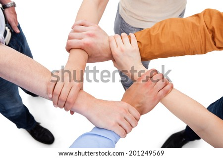 Cropped image of young friends linking hands in team over white background
