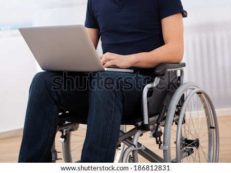 Cropped image of young handicapped man using laptop while sitting on wheelchair at home - stock photo