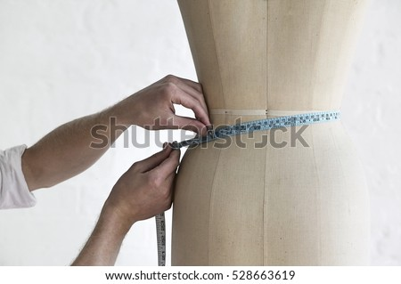 Cropped image of young male tailor measuring mannequin's waist in fashion studio
