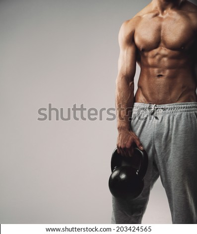 Cropped image of young man in sweatpants holding kettle bell. Crossfit workout theme on grey background work with empty copy space for your text. - stock photo