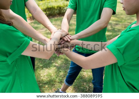 Cropped image of young people in green t-shirts stacking hands in the park - stock photo