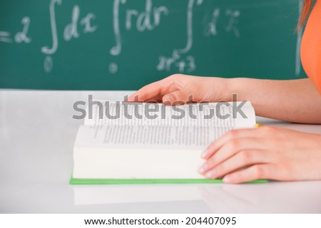 Cropped image of young university student reading book in classroom - stock photo