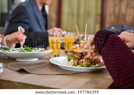 Cropped image of young woman having burger with colleagues at cafe - stock photo