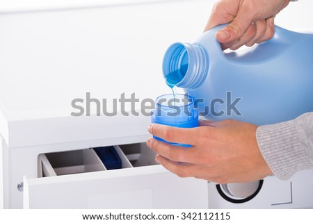 Cropped image of young woman's hand pouring detergent in lid with washing machine in background - stock photo