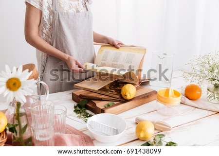 Cropped image of young woman standing indoors near table with a lot of citruses holding cooking book.