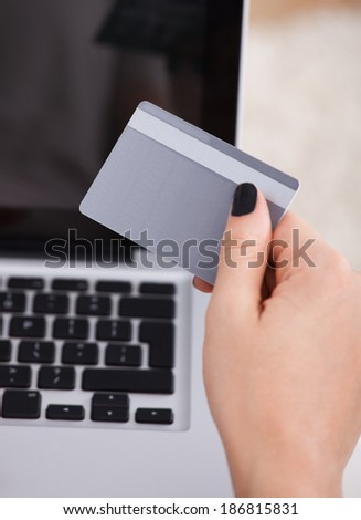 Cropped image of young woman using credit card and laptop to shop online - stock photo
