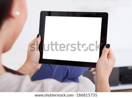 Cropped image of young woman using digital tablet at home - stock photo