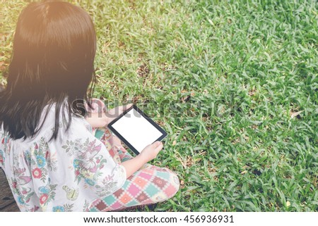 Cropped image of young woman using digital tablet with blank screen at green lawn. vintage filter effect. - stock photo