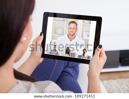 Cropped image of young woman using tablet for video conference at home - stock photo