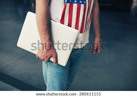 Cropped image university student holding metal color compact notebook in the hand, young freelancer or businessman hands holding close laptop computer, copy space for your text message, filtered image - stock photo