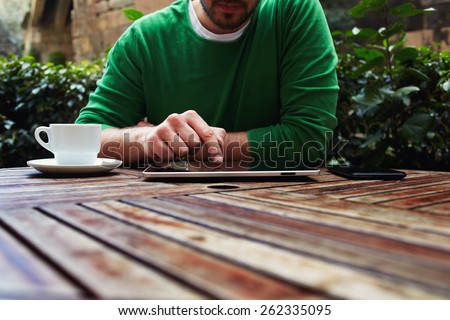 Cropped image young man sitting at the table with cup of coffee, digital tablet and smart phone, man's hands typing message on touch screen tablet while sitting on balcony terrace with plants - stock photo