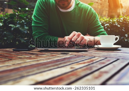 Cropped image young man sitting at the table with cup of coffee, digital tablet and smart phone, man's hands typing message on touch screen tablet while sitting on balcony terrace, flare sun - stock photo