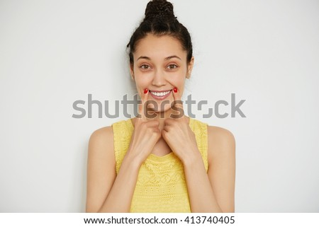 Cropped isolated shot of funny young brunette female wearing bun and yellow top, looking and smiling at the camera touching edges of her lips. Beautiful girl posing against white studio background   - stock photo