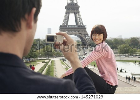Cropped man photographing woman in front of Eiffel Tower - stock photo