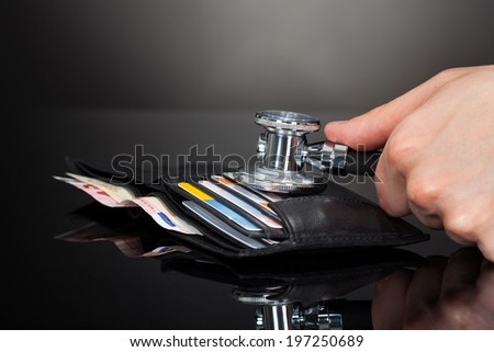 Cropped of man's hand examining wallet with stethoscope at desk against black background - stock photo
