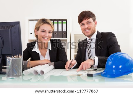 Cropped overhead view of a male and female architect discussing a set of blueprints spread out on a table - stock photo