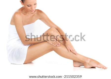 cropped picture of young beautiful woman in cotton towel. closeup of pretty girl sitting on white background - stock photo