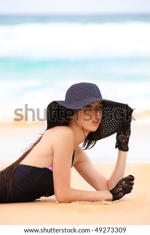 Cropped portrait of an attractive young woman wearing a black one-piece swimsuit, hat, and lace gloves. She is lying in the sand at the beach and staring off into the distance. Horizontal shot.