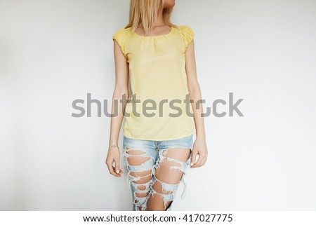 Cropped portrait of beautiful teenage girl looking away while posing against white studio background. Close up view of young female trying on ripped jeans and yellow top during shopping in the mall  - stock photo