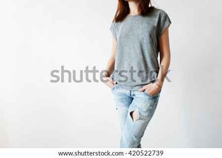 Cropped portrait of cute Caucasian teenage girl with long dark hair standing against white concrete wall. Close up of attractive young woman in gray copy space T-shirt for your advertising content - stock photo