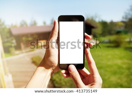 Cropped portrait of female checking for internet connection on mobile phone while resting in the countryside. Close up shot of woman holding cell phone against green nature background. Selective focus - stock photo
