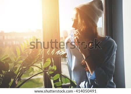 Cropped portrait of female designer discussing new collection on cell phone while sitting at the window. Woman freelancer enjoying sunshine talking on mobile phone and appointing meeting with clients - stock photo