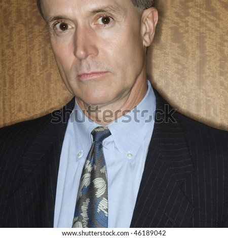 Cropped portrait of intense-looking Caucasian businessman looking into the camera. Square shot. - stock photo