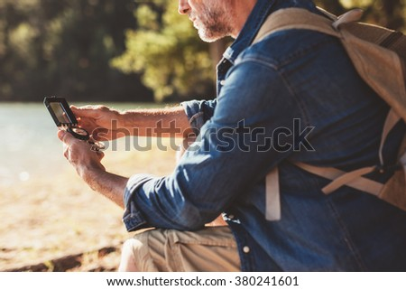 Cropped portrait of mature man sitting at a lake using a compass for navigation. Hiker man searching direction with a compass outdoors. - stock photo