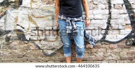 Cropped portrait of stylish person in casual clothes: black t-shirt, plaid shirt  and ripped jeans standing against colourful urban city brick wall background.