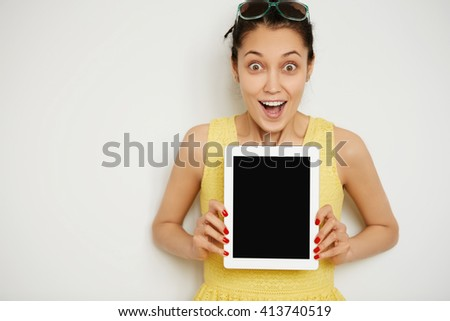 Cropped portrait of young beautiful astonished female holding and showing blank tablet computer with copy space for your text, looking in surprise at the camera isolated against white background - stock photo