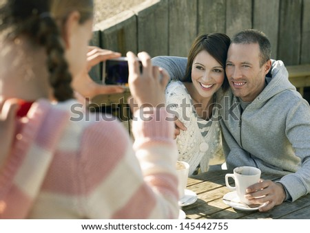 Cropped preteen girl photographing parents sitting at outdoor table - stock photo