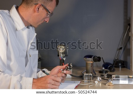 Cropped profile of a researcher in a lab coat and goggles, making notes on an experiment. He is surrounded by scientific equipment. Horizontal format. - stock photo