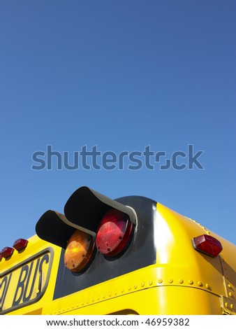 Cropped rear view of a school bus. The taillights are highlighted in the image. Vertical shot. - stock photo