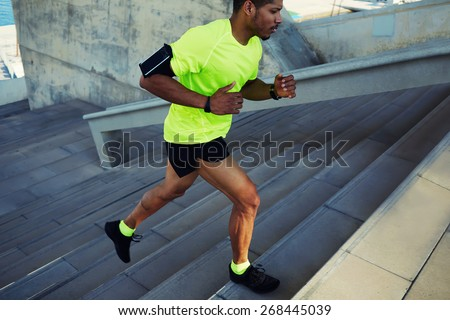 Cropped shot male dark-skinned athlete running up a flight of stairs with speed, sporty young man in fluorescent t-shirt training or working out outdoors while jogging up the steps, filtered image - stock photo