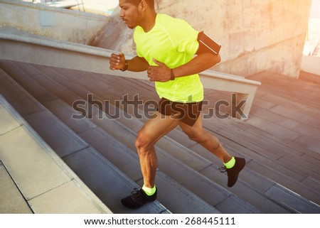 Cropped shot male dark-skinned athlete running up a flight of stairs with speed, sporty young man in fluorescent t-shirt training or working out outdoors while jogging up the steps, flare sun - stock photo