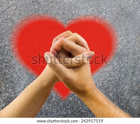 Cropped shot of a couple holding hands with heart painted on a wall - stock photo