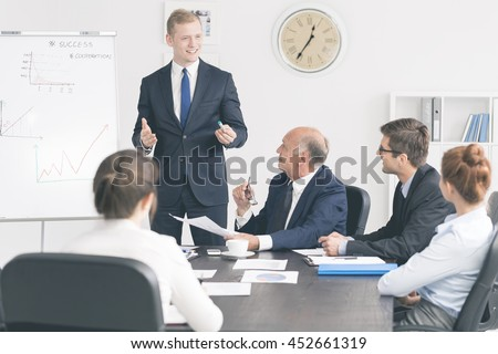 Cropped shot of a handsome employee giving a presentation to the board - stock photo
