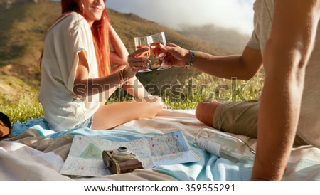 Cropped shot of a man and woman toasting wine while on a picnic. Young couple enjoying a picnic outdoors with wine on a summer day. - stock photo