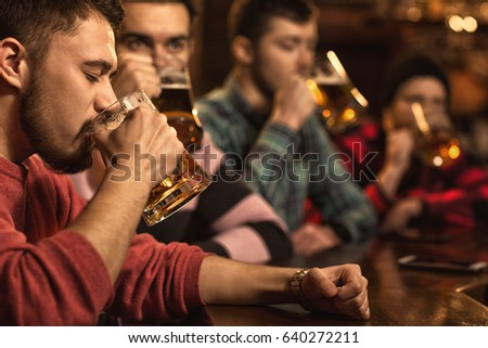 Cropped shot of a man drinking delicious freshly brewed beer sitting at the bar with his friends copyspace enjoyment alcohol refreshing delight pleasure relaxation partying drinks celebration people