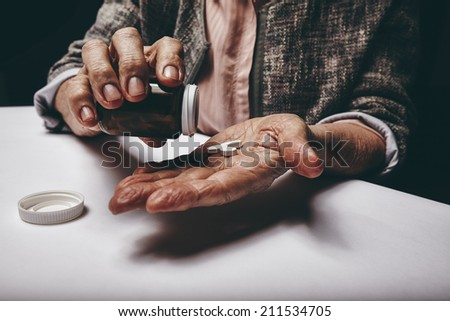 Cropped shot of a old woman sitting at a table shaking a pill out of a pill bottle. Focus on hands. Senior female taking medicine. - stock photo