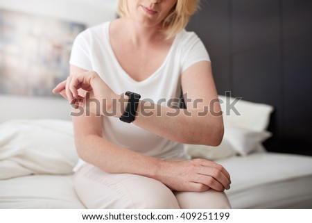 Cropped shot of a woman sitting on bed checking time on her wrist watch, she is in bedroom at home. - stock photo
